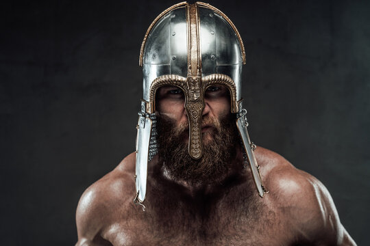 Furious and bearded nordic barbarian with metal helmet on him posing in dark background.