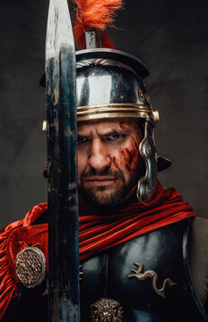 Serious and angry roman soldier dressed in dark armour with helmet and red mantle posing looking at camera and holding a sword.