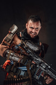 Portrait of guy with blood on his head in dirty armour holding shotgun poses in dark background with angry face.