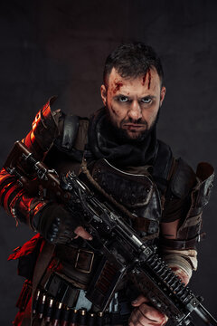 Dressed in dirty clothing with dark armour bearded survivor holding shotgun poses in dark background with serious face.