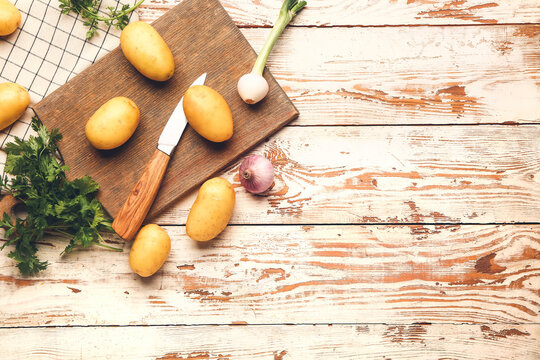Raw potatoes with knife and cutting board on wooden table