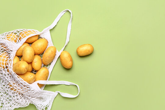 String bag with raw potatoes on color background