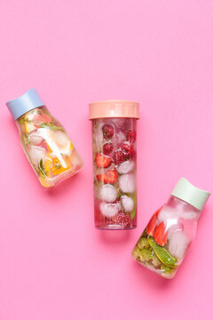 Bottles of infused water with citruses and berries on color background