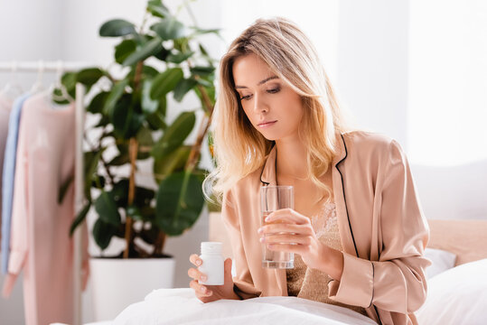 woman looking at jar with pills and holding glass of water on bed