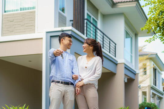 Portrait of Asian young couple standing and hugging together and holding house key looking happy in front of their new house to start new life. Family, age, home, real estate and people concept..
