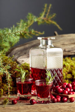 Cranberries and cranberry liquor on an old wooden table.