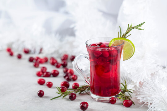 Christmas cranberry drink with berries, lime, and rosemary.
