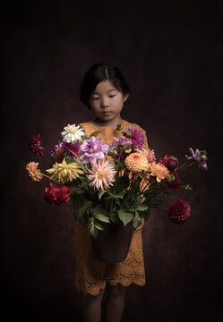 girl holding a large arrangement of colorful dahlia flowers inher arms in dark classic  painterly renaissance style