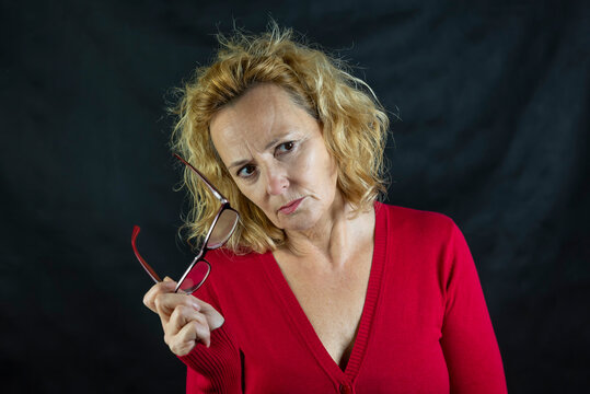Middle-aged blonde woman looks with an angry expression holding up her glasses dressed in a red sweater on a dark background