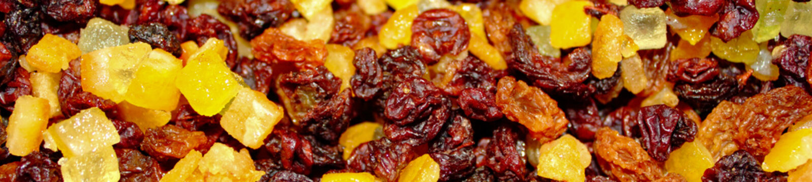 panoramic close up of dried  red and yellow raisins, currants, sultanas, mixed orange , lemon and lime peel, and zest, cranberries, and suet . Ingredients for mince meat for pies and Christmas cake.