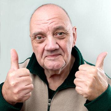 portrait homme âgé deux pouces en l'air sur fond gris