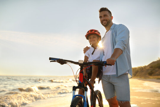 Happy father teaching son to ride bicycle on sandy beach near sea at sunset