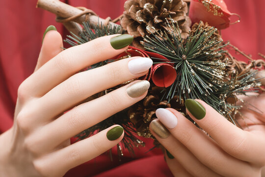 Female hands with Christmas nail design. Green and gold nail polish manicure. Female hands hold New Year decoration.