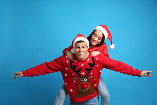 Couple in Christmas sweaters and Santa hats on blue background