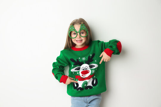 Cute little girl in Christmas sweater and party glasses on white background