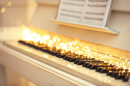 White piano with fairy lights and note sheets closeup. Christmas music