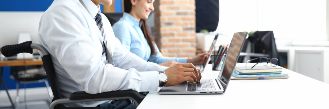 Young smiling man in wheelchair works at laptop in office with woman colleague. Work for disabled people in business sphere concept.
