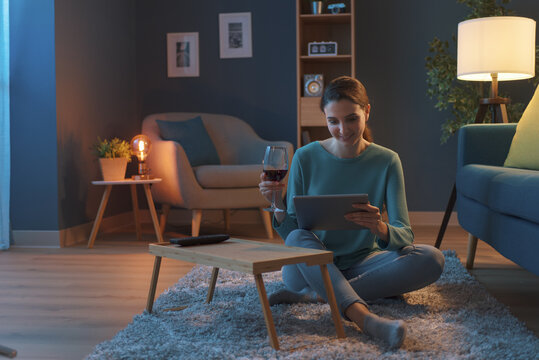 Woman having a glass of wine and connecting online
