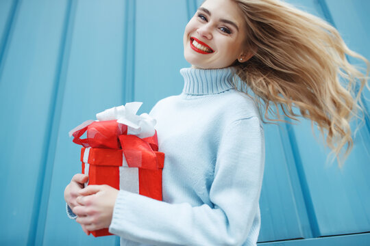 Happy blonde woman in holding gift box and looking at camera while enjoys over blue background. High quality photo.