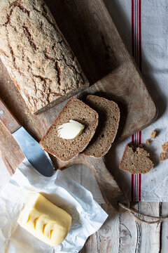 From above loaf of tasty ryecorn bread placed on cloth napkin near spoon of grain on wooden background
