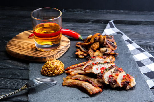 Roasted meat served with fried mushrooms and slice of bacon, mustard and glass of bourbon