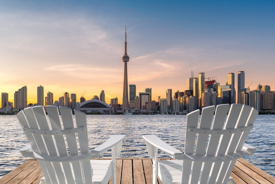 Toronto skyline in wooden pier with white chairs at sunset in Toronto, Ontario, Canada.