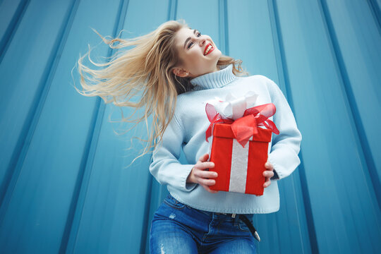 Beautiful elegant young blonde woman holding a gift box. Christmas photos, gifts. High quality photo