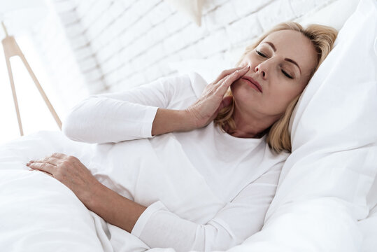 Woman in white bed with severe pain in her teeth.