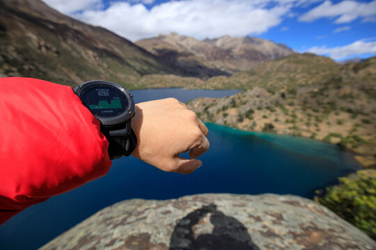 Hiker on high altitude mountain top checking the altitude on the sports watch