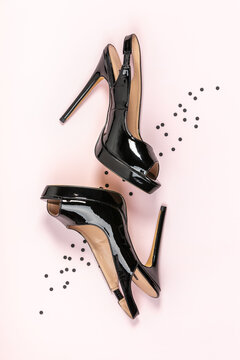 Black women high heel shoes and black confetti on pink background. Flat lay, top view trendy beauty female background.