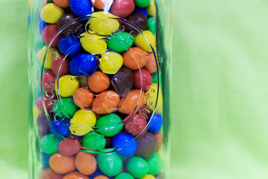 Recyclable transparent glass bottle filled with colored chocolate balls with green background. Sweets for kids concept