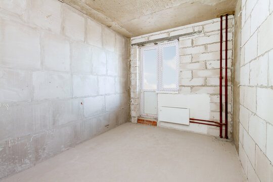 Being renovated house of residential apartment building interior in progress with windows and white brick concrete wall