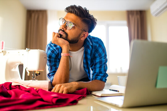 indian tailor asian man designer sewing clothes on sewing machine next to laptop home apartment workplace