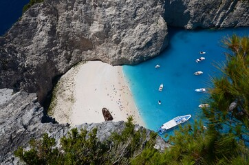 Navagio beach on Zakynthos island, Greece. Blue sky, sunny day, beach, ship wreck, boats in the bay, white limestone cliffs.