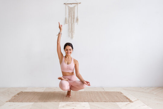 Beautiful well-groomed young woman yoga teacher in pink suit doing samatvamasana sitting on rug on floor In sports hall on background of white wall. Woman performs complicated asana. Advertising space