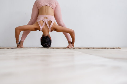 Young unidentified slim woman brunette yoga lover in pink costume doing prasarita padottanasana while standing on rug on floor on white wall. Yoga instructor does an advanced asana. Advertising space