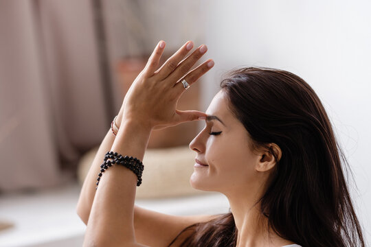 Side view of a beautiful concentrated young woman-amateur yoga meditator clasping her hands with eyes closed in a cozy home environment. Yoga and relaxation. Harmony and health concept