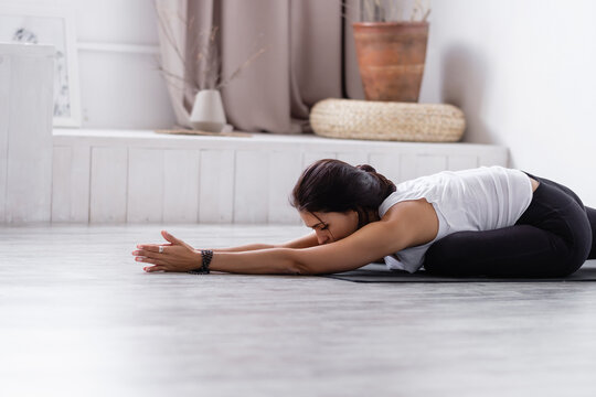 Side view of flexible young slim unidentified woman doing stretching for back and legs while sitting on rug on floor at home. Concept of rejuvenation of joints and circulatory system. Pilates and Yoga