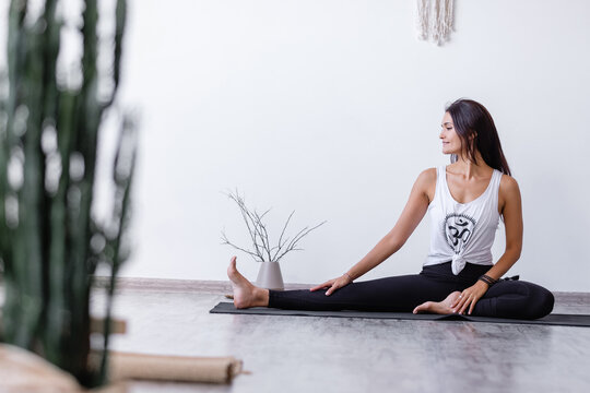 Charming woman brunette yoga lover doing Upavishta Konasana sitting on rug on floor in cozy room. Blood circulation in pelvic region stimulates activity of ovaries and removes gynecological problems