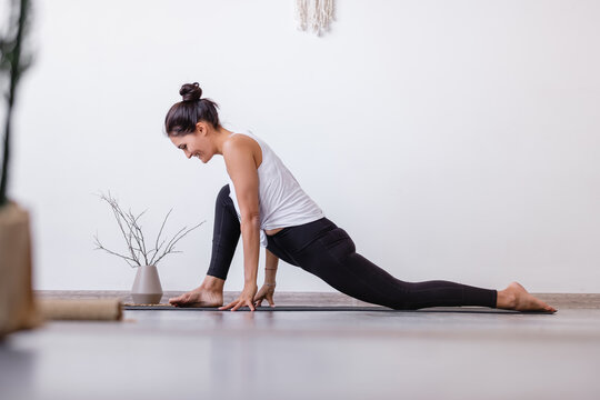 Relaxe harmonious beautiful brunette woman yoga instructor standing in anjaneyasana pose, Horse rider exercise on wooden floor at workout in white yogi classroom. Health and Spirit Improvement Concept