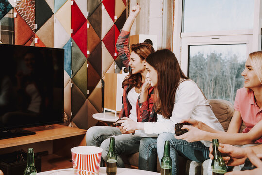 Women are sitting on the couch watching the screen