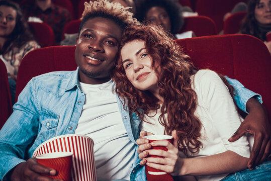 Black man hugging woman and watching movie.
