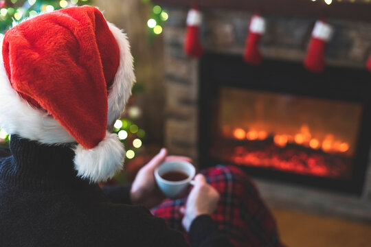 Man with cup coffee, tea in santa claus hat sitting and warming at winter evening near fireplace flame, covered christmas plaid