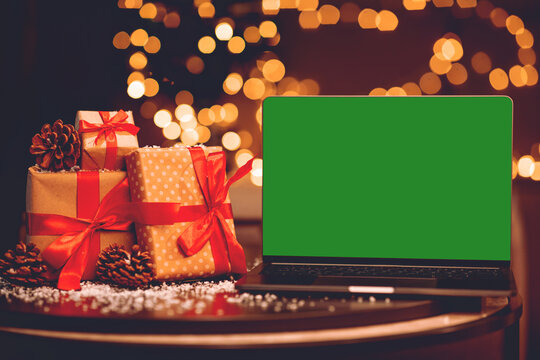 Laptop with blank green screen on snowy table with gifts and pine cones on blurred Christmas background with garland