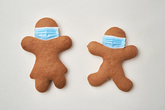 Top view of two gingerbread man with face masks