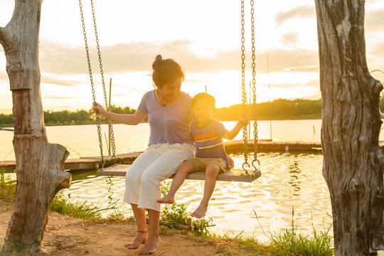 mother and child ride on wood swing in a summer at sunset time.
