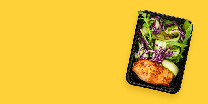Healthy meal prep containers with  chicken and vegetable salad. Yellow background. Top view