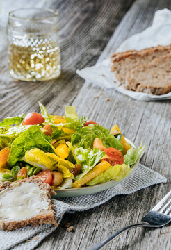 Lettuce with tomatoes, peppers and dried apricots, whole grain bread, and apple juice