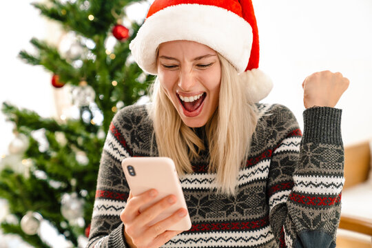 Excited woman in christmas santa hat making winner gesture
