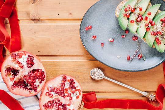 Halved pomegranate and spoon with seeds placed near plate with delicious avocado toast on wooden table